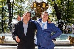 在喷泉附近冷却新郎和他的父亲在夏天公园 免版税库存图片