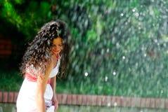 在喷泉附近的美丽的女孩 库存图片