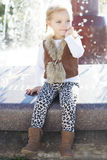在喷泉,秋天时间附近的小女孩 免版税库存照片