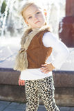 在喷泉,秋天时间附近的小女孩 免版税图库摄影