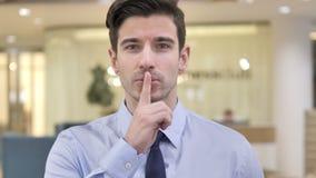 在嘴唇的手指,打手势沈默的商人 股票录像