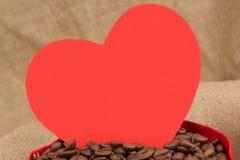 在囊的红色心脏用coffe豆 免版税库存图片