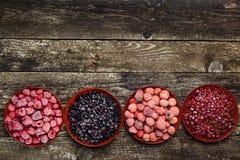 在四个碗的冷冻莓果在木背景 顶视图 文本的空间 免版税图库摄影