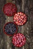 在四个碗的冷冻莓果在木背景 顶视图 库存照片