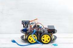 在四个轮子和各种各样的缆绳的机器人与大蓝色导线 库存图片