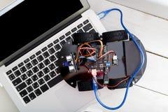 在四个轮子的机器人连接了到膝上型计算机通过蓝色导线 库存图片