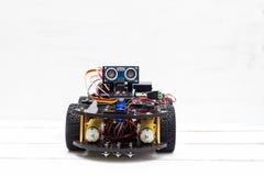 在四个轮子的骑马机器人在轻的背景 图库摄影
