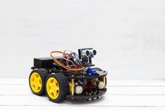 在四个黄色轮子的机器人在轻的背景 库存图片