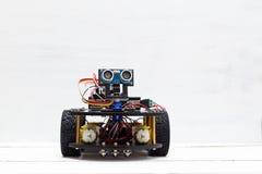 在四个黄色轮子的骑马机器人在轻的背景 库存照片