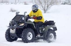 在四元组的自行车驱动器乘坐雪跟踪 免版税库存照片