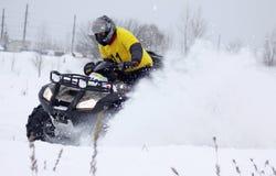 在四元组的自行车驱动器乘坐雪跟踪 免版税库存图片