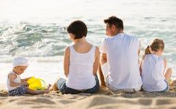 在四口之家的后面看法坐海滩 免版税库存照片