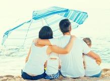 在四口之家的后面看法坐海滩 免版税库存图片