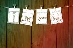 在四张华伦泰` s卡片的爱热的消息说`我爱你,婴孩! 在土气漂流木头纹理背景的` 库存照片