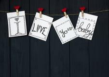 在四张华伦泰` s卡片的滑稽的消息说`我爱你,婴孩! `自然垂悬在土气漂流木头的绳子和红色别针发短信 免版税库存照片