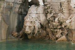 在四条河的喷泉的狮子雕象在纳沃纳广场在罗马 免版税图库摄影