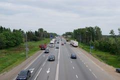 在四车道的高速公路的汽车通行 库存图片
