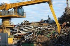在回收工厂的金属的黄色起重机 库存图片