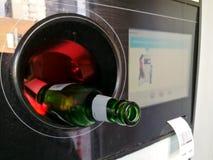 在回收的自动反向贩卖机插入的啤酒瓶 图库摄影