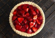 在困厄的木表上的一个新鲜的草莓饼 图库摄影