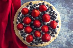 在困厄的蓝色木表上的一个草莓和蓝莓新鲜的夏天饼 免版税库存图片
