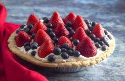 在困厄的蓝色木表上的一个草莓和蓝莓新鲜的夏天饼 库存照片
