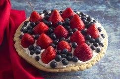 在困厄的蓝色木表上的一个草莓和蓝莓新鲜的夏天饼 免版税图库摄影