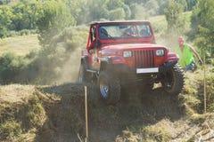 在困难的地形的红色SUV 图库摄影