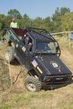 在困难的地形的黑SUV。垂直。 免版税库存图片