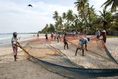 在困难的日子运作后,渔夫在斯里兰卡延长他们的在Uppuveli海滩的网 免版税库存照片