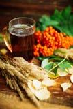 在围巾的绿色圈子,与槭树叶子的在雨以后的窗口和下落秋天/季节,当您需要温暖的饮料时 库存图片