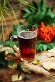 在围巾的绿色圈子,与槭树叶子的在雨以后的窗口和下落秋天/季节,当您需要温暖的饮料时 库存照片