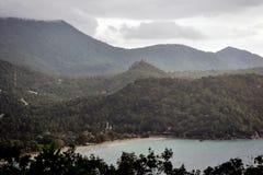 在围拢一个小海湾的海滩的热带雨的密集的密林 免版税库存照片