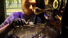 在围裙的一男性barista检查在烧烤咖啡,慢动作的咖啡豆 影视素材