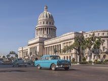 在国会大厦前面的经典汽车Havana.Cubans的保留千位他们运行,既使当零件未做在数十年,并且他们成为国家(地区)的图标 古巴 免版税库存照片