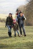 在国家步行的家庭在冬天 免版税库存照片