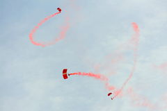 在国庆节游行(NDP)排练期间的红色狮子尽量延缓张伞的跳伞运动2013年 免版税库存照片