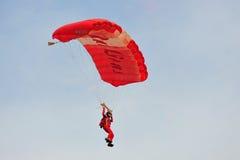 在国庆节游行(NDP)排练期间的红色狮子尽量延缓张伞的跳伞运动2013年 图库摄影