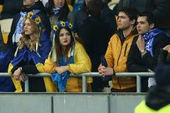 在国民穿戴的发电机Kyiv母爱好者上色了花小环和包裹在乌克兰旗子, UEFA欧罗巴同盟 库存图片