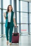 在国际机场走以她的行李和咖啡的少妇去 免版税图库摄影