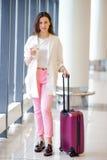 在国际机场走以她的行李和咖啡的少妇去 免版税库存图片