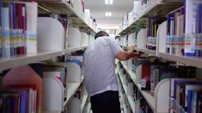 在图书馆书架的男学生寻找的书 股票录像
