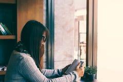 读在图书馆咖啡馆的女孩圣经 库存照片