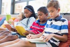 在图书馆教育孩子坐沙发和阅读书 免版税库存照片