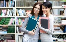 在图书馆的两个女朋友拥抱 免版税图库摄影