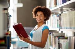 在图书馆的愉快的非洲学生女孩阅读书 免版税库存图片