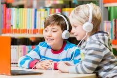 在图书馆里听音频书的孩子 免版税库存照片