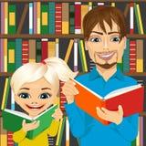 在图书馆里生和他的读有趣的书的女儿 免版税库存图片