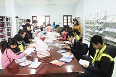 读在图书馆里的学生 免版税图库摄影