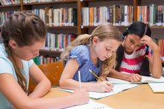 画在图书馆里的逗人喜爱的学生 免版税库存图片